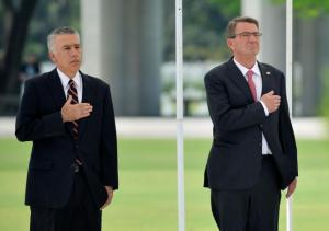 U.S. Defence Secretary Ash Carter (R) and U.S. ambassador to the Philippines Philip Goldberg stand at attention while the American anthem is played at the American cemetery in Taguig, metro Manila April 14, 2016.  REUTERS/Ezra Acaya