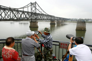 FILE PHOTO: People look through binoculars towards North Korea from the destroyed bridge across Yalu River that once linked North Korea's Sinuiju and Dandong, China's Liaoning province, September 10, 2016. REUTERS/Thomas Peter/File Photo People look through binoculars towards North Korea from the destroyed bridge across Yalu River that once linked North Korea's Sinuiju and Dandong, China's Liaoning province, September 10, 2016. REUTERS/Thomas Peter/File Photo